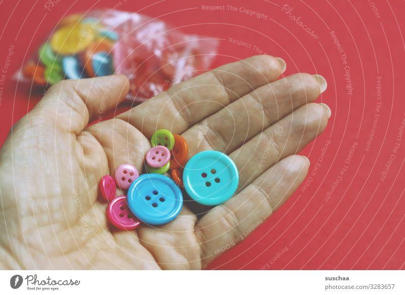 knöpfe Knöpfe Bastelknöpfe Basteln Loch Hand Finger viele mehrfarbig Nähen annähen Bastelzubehör Hintergrund neutral rot Tütchen DIY verschönern