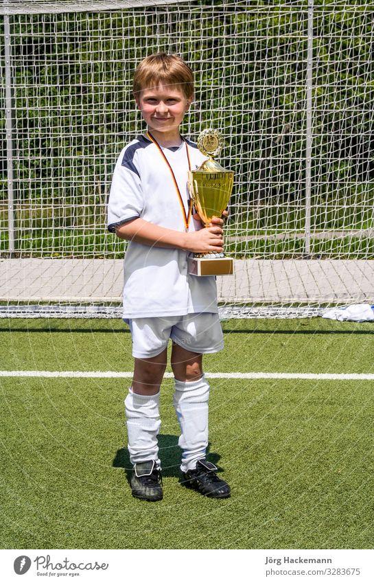 der Junge hält nach dem Spiel stolz den Pokal in der Hand Freude Glück Spielen Club Disco Sport Fußball Kind Freundschaft Kindheit Jugendliche Bewegung Fitness