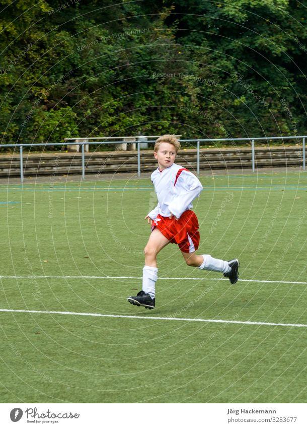 junger Fußballspieler läuft über den Fußballplatz Freude Glück Spielen Club Disco Sport Kind Mensch Junge Kindheit Jugendliche Schuhe Bewegung Fitness