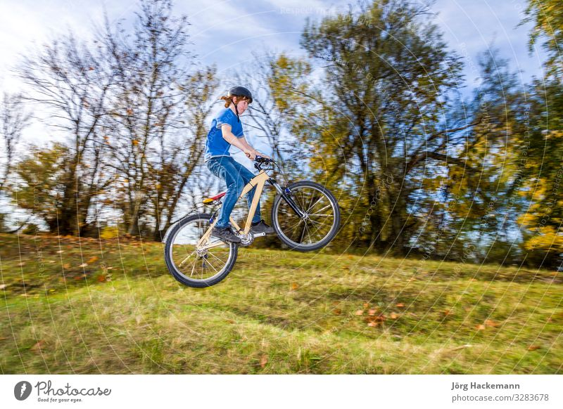 Junge springt mit seinem Geländemotorrad über eine Rampe Freude Glück Sommer Jugendliche Natur Fitness springen BMX Fahrrad passen Training luftgestützt