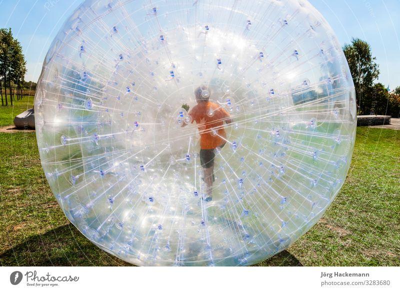 Kinder haben Spaß im Zorbing-Ball Freude Glück Freizeit & Hobby Abenteuer Sommer Sonne Sport Gras Wiese Hügel Kugel Tropfen Bewegung Fitness lachen