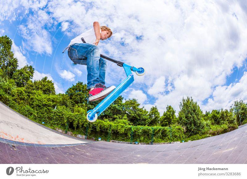Junge mit Roller geht in die Luft Lifestyle Freude Glück Freizeit & Hobby Sport Kind Mensch Mann Erwachsene Kindheit Himmel Wetter Park Bewegung Fitness