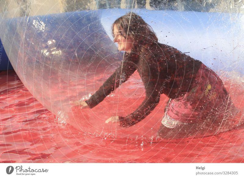 Frau kniet vergnügt in einer großen Plastikkugel im Wasserbecken Mensch feminin Erwachsene 1 45-60 Jahre Bekleidung T-Shirt Rock brünett langhaarig Bubble
