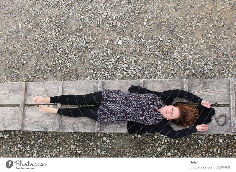 eine bekleidete Frau mit dunkler und gemusterter Kleidung liegt mit geschlossenen Augen auf einem Steg Mensch feminin Erwachsene 1 45-60 Jahre Umwelt Natur