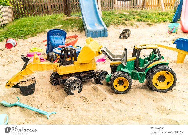 Buntes Spiezeug im Sandkasten Freude Spielen Kinderspiel Sommer Strand Kindergarten Natur Spielzeug Kunststoff positiv gelb grün Hintergrundbild Bagger