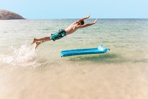 Himmel Ferien & Urlaub & Reisen Jugendliche blau weiß Meer Freude Strand Junge braun springen Wellen Insel Energie Geschwindigkeit niedlich