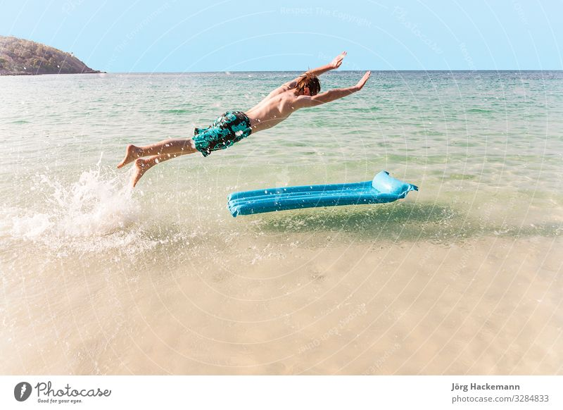Junge mit roten Haaren genießt es, auf der Luftmatratze zu springen Freude Ferien & Urlaub & Reisen Strand Meer Insel Wellen Jugendliche Himmel niedlich