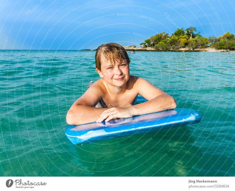 Junge schwimmt auf seinem Surfbrett Freude Glück Erholung Ferien & Urlaub & Reisen Strand Meer Insel Kind Jugendliche Natur Landschaft Himmel Horizont Wärme