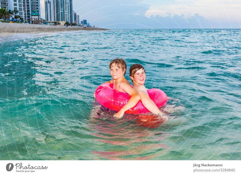 Brüder in einem Schwimmring haben Spaß im Meer Freude Glück schön Haut Erholung Freizeit & Hobby Ferien & Urlaub & Reisen Sonne Wellen Kind Junge Jugendliche