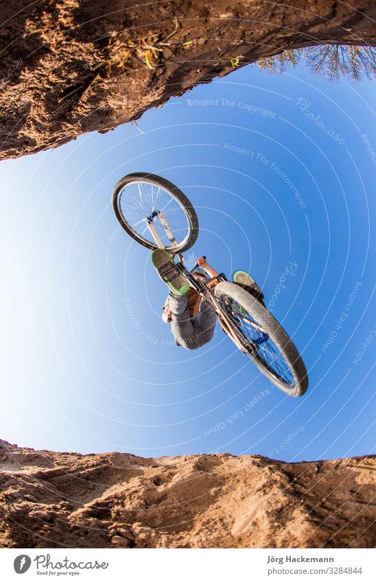 Junge geht mit einem Geländemotorrad in die Luft Lifestyle Freude Glück Freizeit & Hobby Kind Mensch Mann Erwachsene Kindheit Jugendliche Himmel Park Bewegung