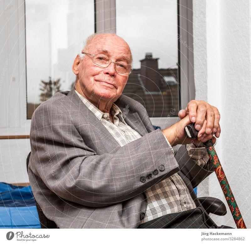 lächelnder älterer Mann sitzt auf dem Stuhl Lifestyle Freude Glück Gesicht Erholung ruhig Ruhestand Mensch Erwachsene Jacke alt Lächeln sitzen klug grau