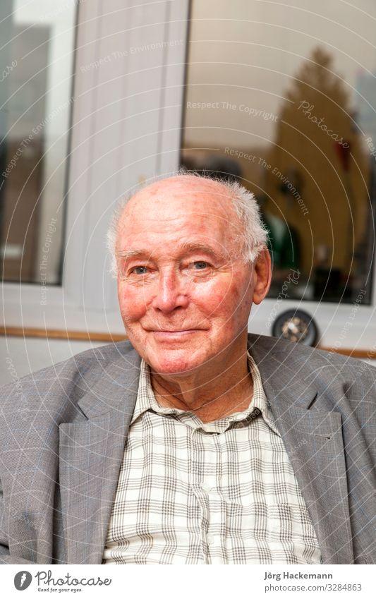 der ältere Mann sitzt am Stuhl und sieht glücklich aus Lifestyle Freude Glück Gesicht Erholung ruhig Ruhestand Mensch Erwachsene Jacke alt Lächeln sitzen klug