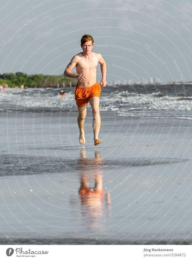 Teenager joggt gerne am Strand entlang Freude Glück Körper Ferien & Urlaub & Reisen Joggen Junge Jugendliche Sand Bewegung Fitness genießen Lächeln lachen