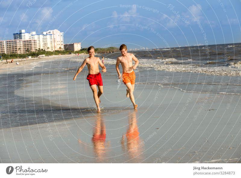 Teenager joggt gerne am Strand entlang Freude Glück Körper Erholung Ferien & Urlaub & Reisen Joggen Junge Jugendliche Sand Bewegung Fitness genießen Lächeln