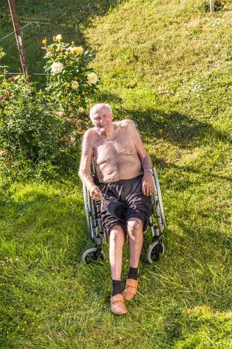 der ältere Mann entspannt sich im Rollstuhl Freude Glück Erholung Sommer Garten Erwachsene Wärme Gefühle achtzig Brille neunzig in den Ruhestand getreten Senior
