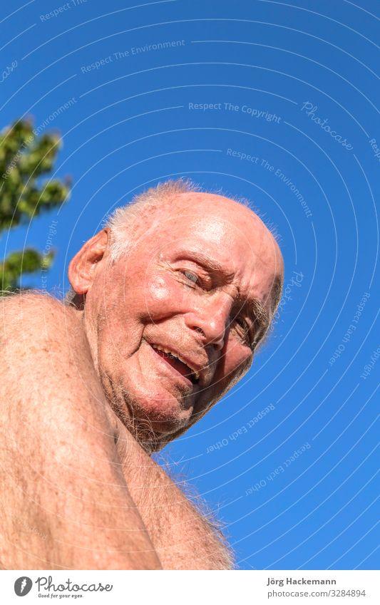 der Senior sitzt auf dem Stuhl im Garten Lifestyle Freude Glück Erholung Sommer Sonne Ruhestand Mann Erwachsene Großvater Natur Himmel alt Lächeln blau grün