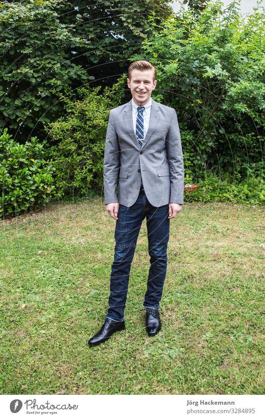 elegant gekleideter Jugendlicher posiert im Garten Freude Glück Anzug Krawatte Lächeln lachen stehen Stolz attraktiv clever angekleidet achtzehn gutaussehend
