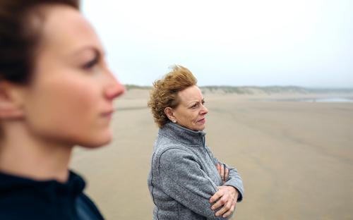 Zwei Frauen, die auf das Meer schauen. Lifestyle schön Meditation Strand Mensch Erwachsene Mutter Großmutter Familie & Verwandtschaft Sand Herbst Wind Nebel