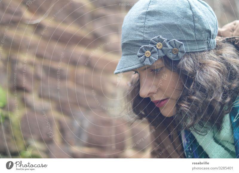 junge, hübsche, lockige, brünette Frau mit Hut, Jacke und Halstuch im Profil schaut nachdenklich nach unten Locken denken grübeln Schal draußen draussen Herbst