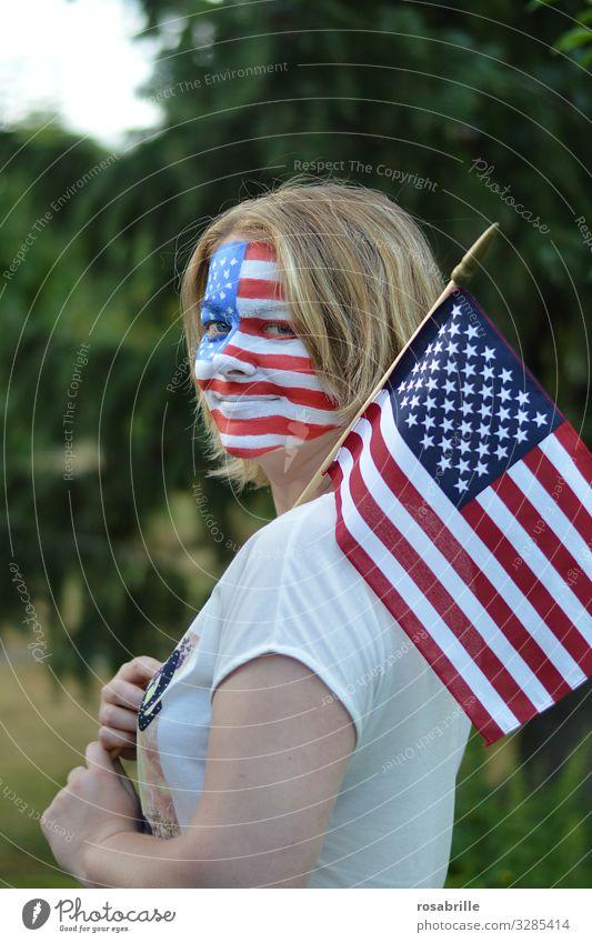 Farbe bekennen | wörtlich genommen | patriotische junge blonde Frau mit amerikanischer Fahne und Flagge aufs Gesicht gemalt im Freien hofft auf den Sieg ihrer Fußballmannschaft