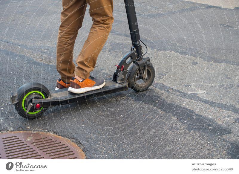 Roller mit Luftreifen asphaltierter Gullydeckel braune Hose Mann Erwachsene 13-18 Jahre Jugendliche 18-30 Jahre 30-45 Jahre Straße Tretroller Turnschuh Spielen