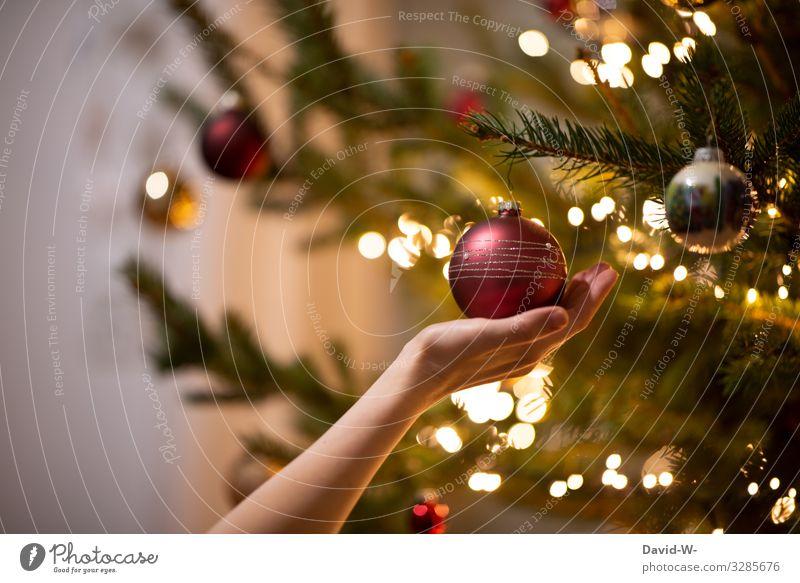 Hand hält zur Weihnachtszeit eine Christbaumkugel vom Tannenbaum Weihnachten schmücken Weihnachtsbaum dekoration Weihnachtsbeleuchtung Lichterkette besinnlich