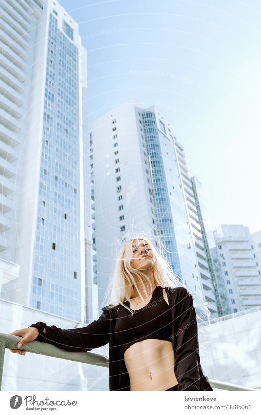 Frau in Sportkleidung steht vor den Gebäuden der Stadt Bauchmuskeln Aktion Erwachsene Athlet blond Körper Kaukasier Großstadt Kerngehäuse Gesundheit sportlich
