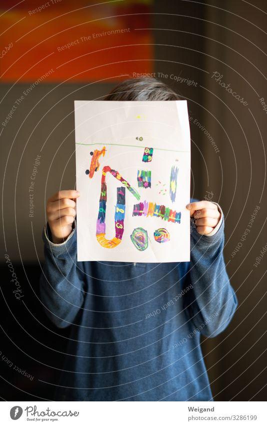 Junge mit selbstgemaltem Bild Kindererziehung Bildung Kindergarten Schule lernen Klassenraum Schulkind Schüler 1 Mensch zeichnen Papier Farbfoto Innenaufnahme