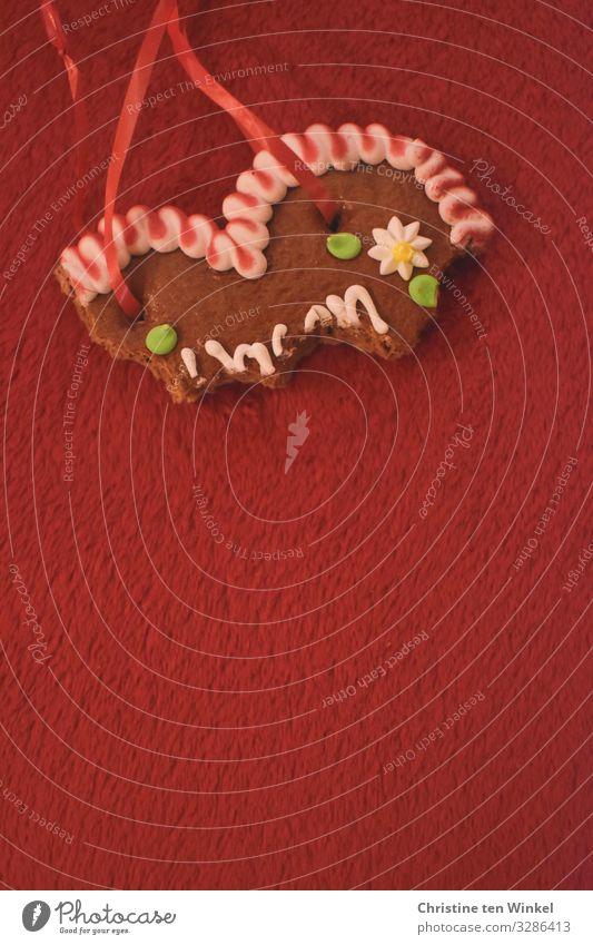 angebissenes Lebkuchenherz auf rotem Untergrund Lebensmittel Teigwaren Backwaren Lebkuchenherzen Ernährung Kitsch Krimskrams Souvenir Herz Fröhlichkeit trendy