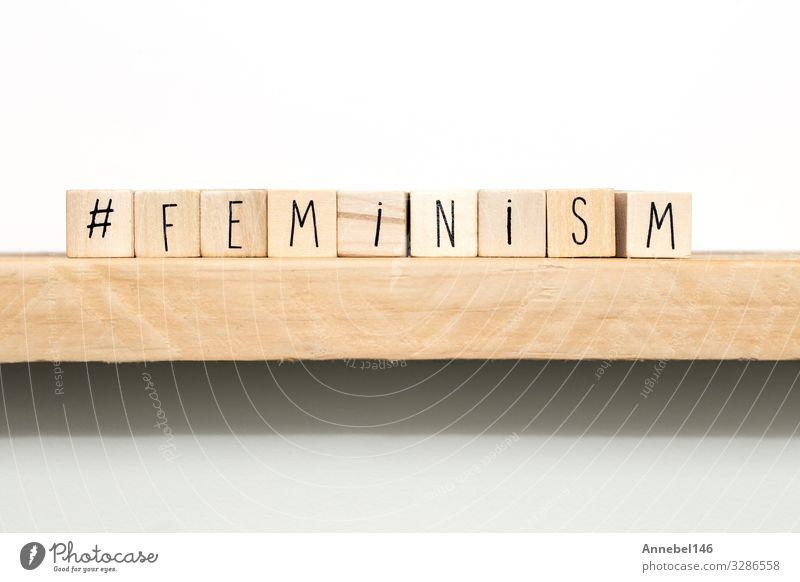 Holzwürfel mit einem Rautezeichen und dem Wort Feminismus Schule Frau Erwachsene Medien Buch Papier schwarz weiß Idee Emanzipation Bildung Definition Brief
