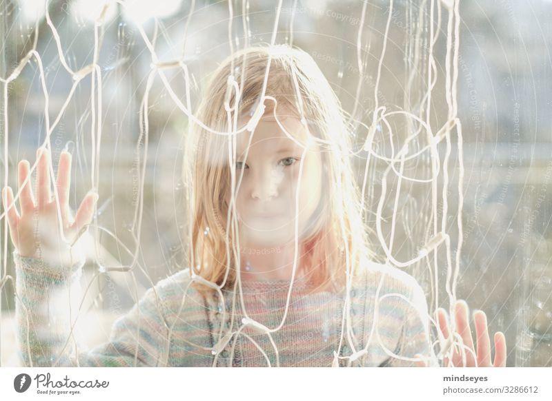 Mädchen steht hinter einer Glasscheibe Spielen Häusliches Leben Lichterkette 1 Mensch 3-8 Jahre Kind Kindheit beobachten träumen Traurigkeit hell natürlich