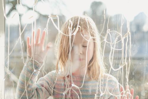 Mädchen steht im Freien hinter einer Glasscheibe mit geschlossenen Augen Häusliches Leben Haus Dekoration & Verzierung Lichterkette 1 Mensch 3-8 Jahre Kind