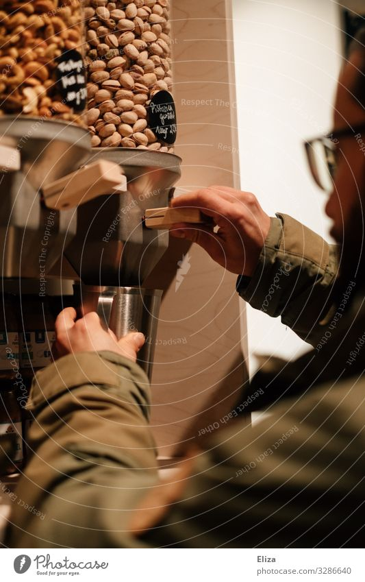 Ein Mann der sich Nüsse aus einem Behälter in einem verpackungsfreien Supermarkt abfüllt; Nachhaltigkeit maskulin kaufen unverpackt ohne Verpackung