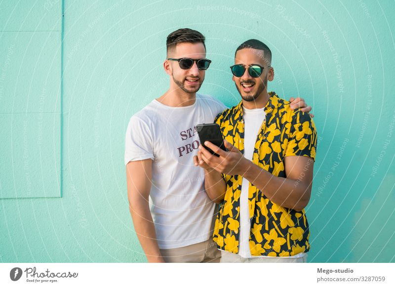 Ein schwules Paar, das Zeit miteinander verbringt, während es telefoniert. Lifestyle Glück Leben Freizeit & Hobby Freiheit Handy PDA Homosexualität Mann