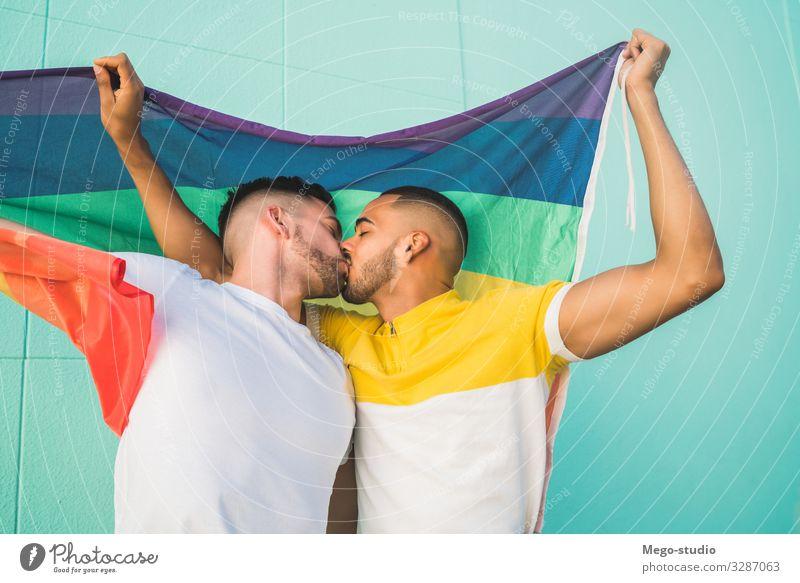Schwules Paar umarmt und zeigt seine Liebe mit der Regenbogenfahne. Lifestyle Glück Freiheit Feste & Feiern Mensch Homosexualität Mann Erwachsene Partner Fahne