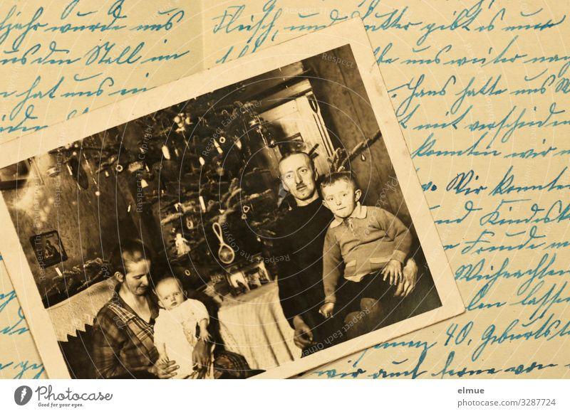 ein altes Foto, was auf einem Schriftstück liegt, zeigt Vater, Mutter und zwei Kinder vor einem geschmücktes Weihnachtsbaum sitzend Schriftzeichen einfach