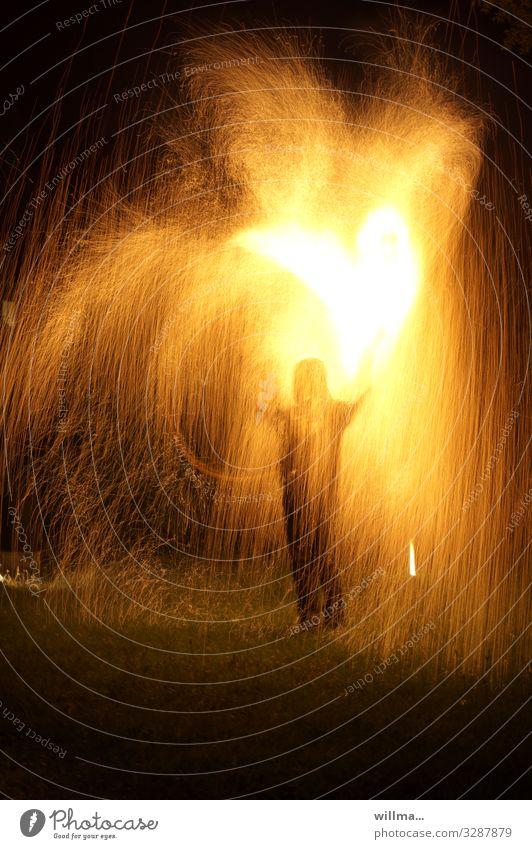 Mensch steht mitten im Funkenregen mit brennendem Herz brennendes Herz Feuer Feuerregen heiß Liebe Valentinstag Verliebtheit Herz in Flammen anzünden