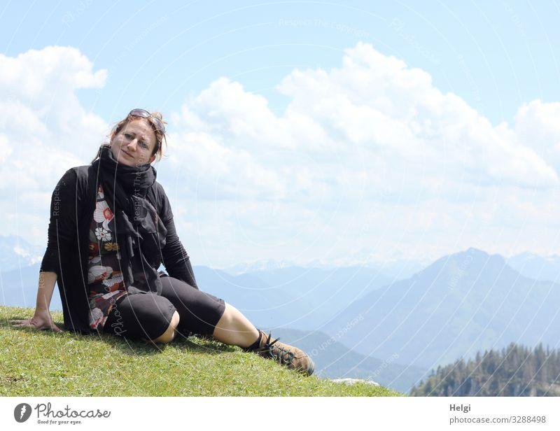 eine Frau sitzt bei schönem Wetter auf einem Berg, im Hintergrund sieht man die Alpen Mensch feminin Erwachsene 1 45-60 Jahre Umwelt Natur Landschaft Pflanze
