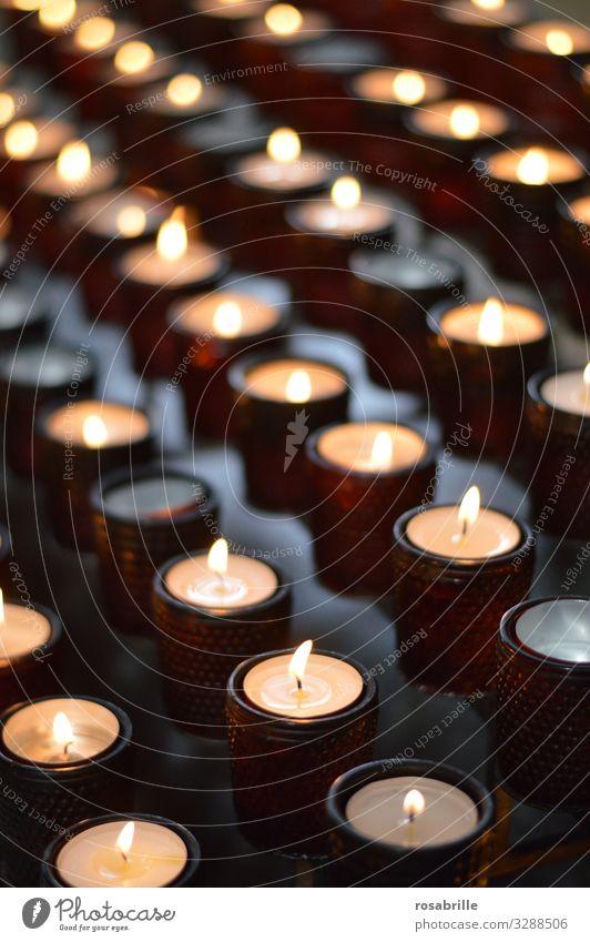 Reihen mit Kerzen in Gläsern in einer Kirche als Symbol fuer Gebet Feuer leuchten dunkel heiß hell viele Vertrauen trösten dankbar Ehrlichkeit Hoffnung Glaube