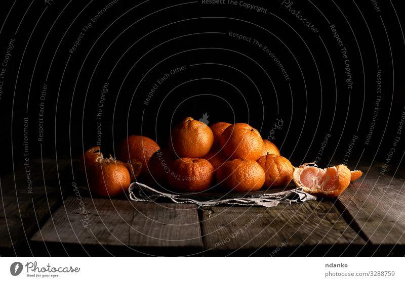 Haufen ungeschälter runder, reifer Orangenmandarinen Frucht Dessert Ernährung Vegetarische Ernährung Saft Teller Tisch Holz frisch natürlich saftig gelb grau