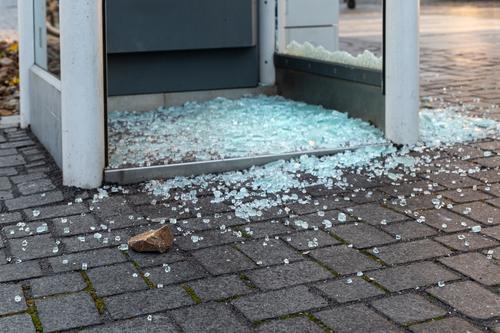 Glasscherben und Stein vor einer Telefonzelle Öffentlich Aggression rebellisch Hemmungslosigkeit Wut trotzig Gesellschaft (Soziologie) protestieren Zerstörung