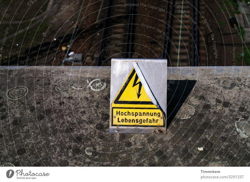Das Schild ernst nehmen Brücke Verkehr Schienenverkehr Gleise Beton Metall Kunststoff Zeichen Schriftzeichen Hinweisschild Warnschild dunkel gelb grau schwarz