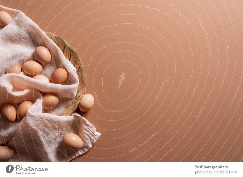 Die Eier stapeln sich auf braunem Grund. Bio-Braune Eier. Frische Eier Lebensmittel Ernährung Diät Gesunde Ernährung natürlich obere Ansicht brauner Hintergrund