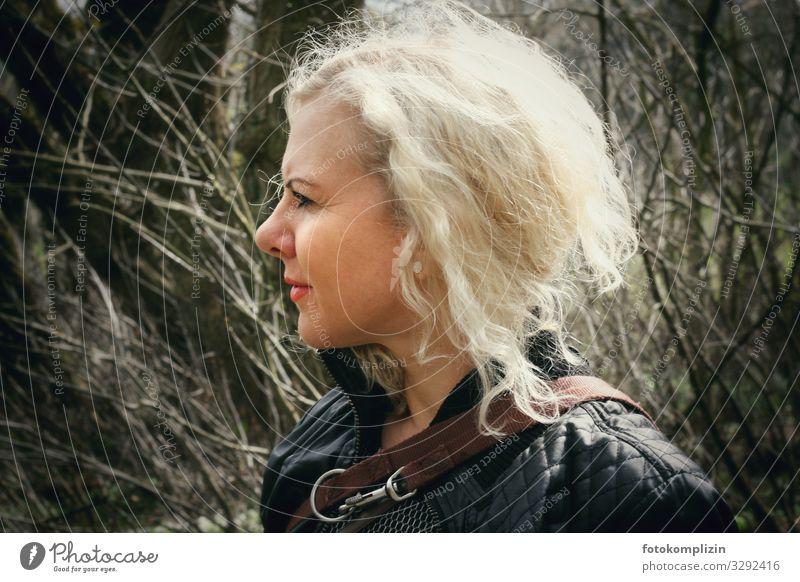 Portrait einer blonden Frau mit Hundeleine vor kahlem Gestrüpp weiblich selbstbewußt Frauengesicht schauen blicken erwarten erwartend blondiert Spaziergang