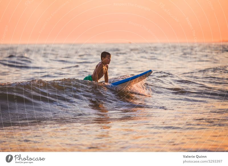Surfen bei Sonnenuntergang Junge 1 Mensch 8-13 Jahre Kind Kindheit Wasser Himmel Horizont Sommer Wellen Strand Badehose Freude Ferien & Urlaub & Reisen