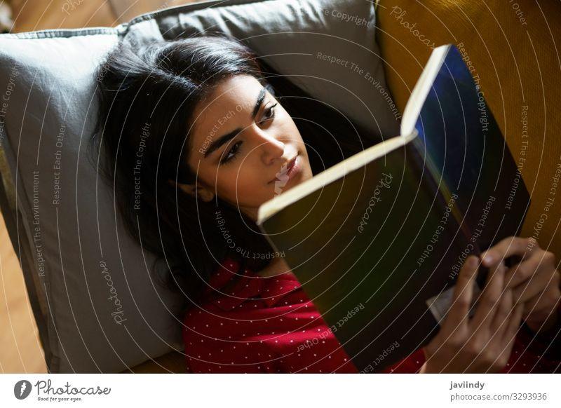 Persische Frau zu Hause beim Lesen auf der Couch Kaffee Lifestyle Haare & Frisuren Erholung Freizeit & Hobby lesen Winter Wohnung Sofa Wohnzimmer Mensch feminin