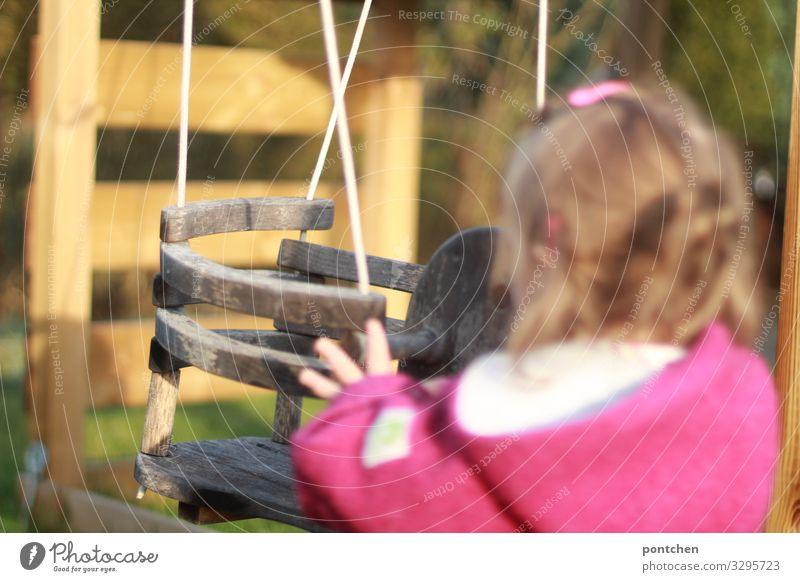Kleinkind steht vor leerer Schaukel und schubst sie an. Kinderspiel Mensch feminin 1 1-3 Jahre schaukeln Holz anschubsen anschieben Hand wollwalk Haarspange