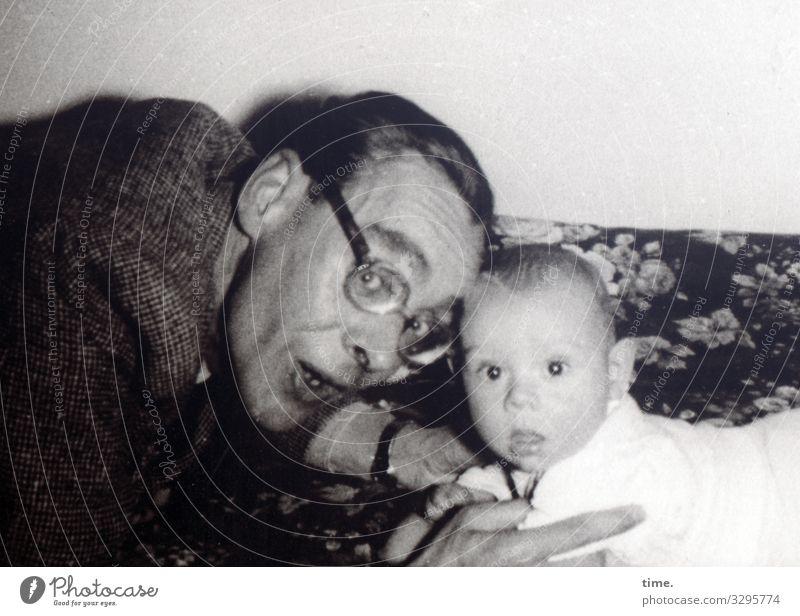 Rampenlicht (I) Häusliches Leben Wohnung Sofa maskulin Baby Mann Erwachsene Mutter 2 Mensch Jacke Brille kurzhaarig beobachten festhalten Blick Wachsamkeit