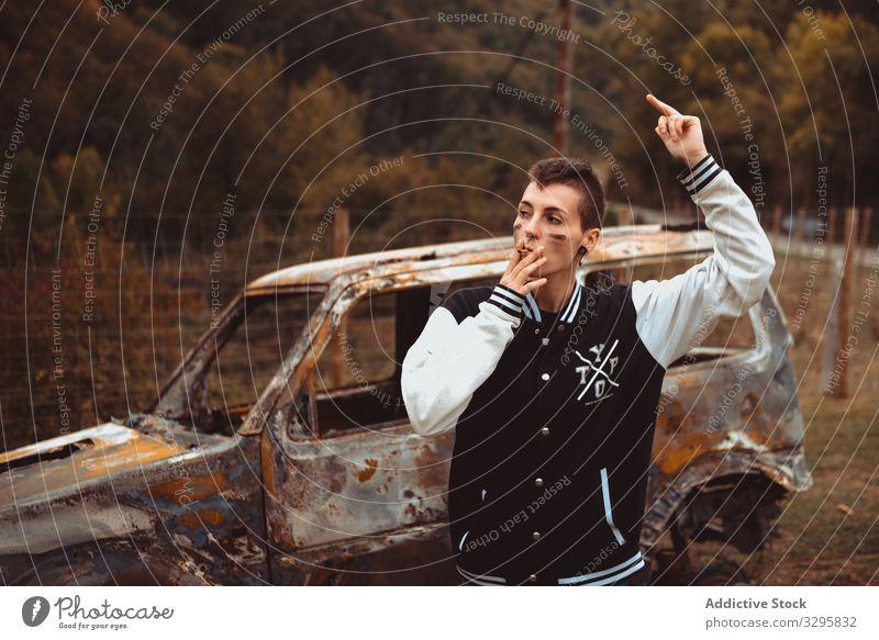 Frau mit Zigarette geht in der Nähe eines verbrannten Autos Rauch laufen auflehnen ruhen PKW rostig Landschaft jung fettarm Lifestyle Freiheit Fahrzeug androgyn