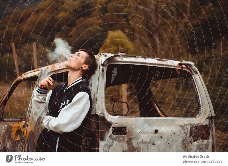 Junge Frau raucht in der Nähe eines beschädigten Autos Zigarette Rauch ausatmen auflehnen PKW rostig Landschaft verbrannt jung fettarm Freiheit Fahrzeug
